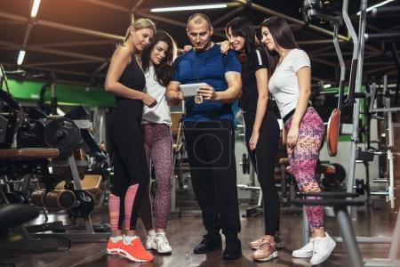 handsome personal trainer using digital tablet, group of sporty women around him in gym