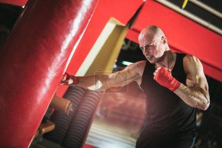 brutal bald man boxing in gym