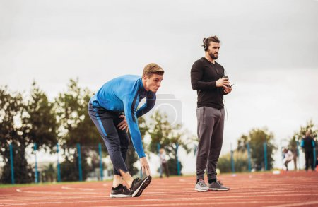 muscular athletic young men stretching out at stadium track