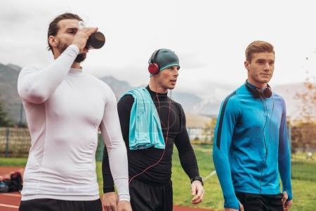 Photo for Three young male athletes walking on stadium track - Royalty Free Image