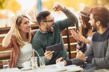 Photo pour Groupe de jeunes gens heureux au café parler et rire ensemble - image libre de droit