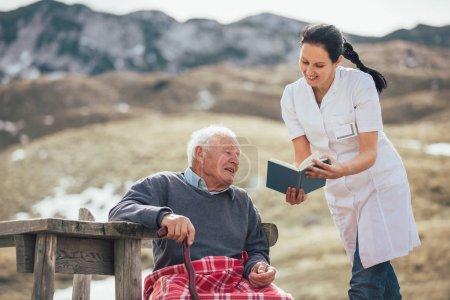 Photo pour Sourire infirmière lecture livre à heureux homme âgé en plein air - image libre de droit