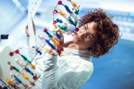 young female scientist looking at DNA in laboratory