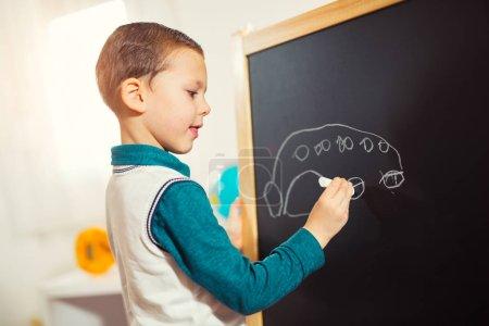 childish scribbles, little boy drawing with chalk on blackboard