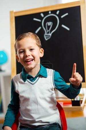 cheering little boy with lightbulb drawn on chalkboard, idea concept