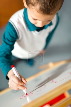 cute little boy drawing on white board with felt pen. Early education concept