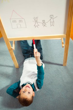 smiling cute little boy drawing on white board with felt pen. Early education concept