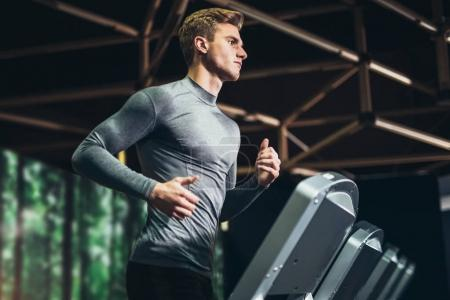 man running in gym on treadmill. Concept for exercising, fitness and healthy lifestyle