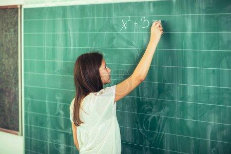 clever cute schoolgirl writing on blackboard with chalk