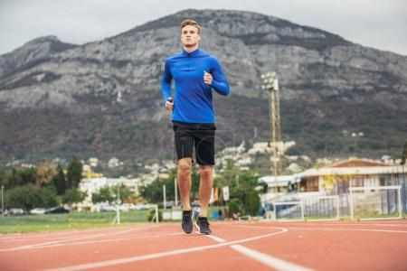 young sporty man jogging on running track