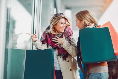 Happy female friends shopping. Two beautiful young women enjoying shopping in city