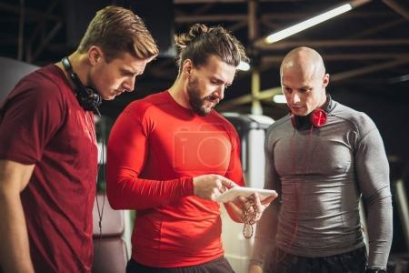 young men and their personal fitness trainer in gym, Trainer showing training plan on phone