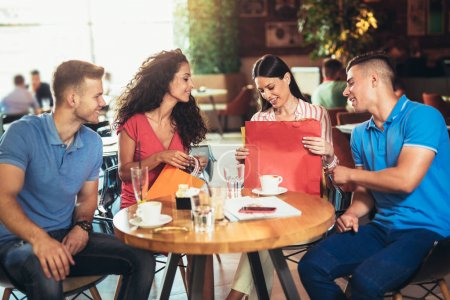 group of happy young people meeting in a cafe after shopping