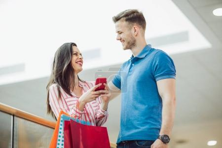 happy young couple with shopping bags and smartphone in mall