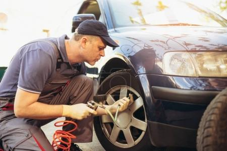 Photo for Mechanic repairman at car tyre, fitting and balancing adjustment - Royalty Free Image