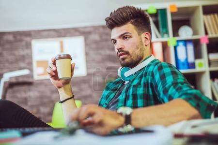 handsome caucasian man at work desk with desktop computer in office