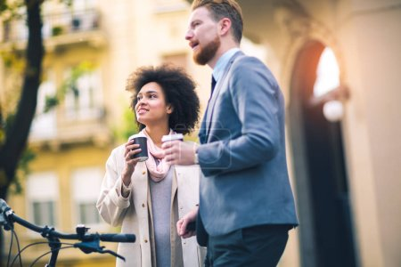 couple of young business people having informal conversation on street, drinking coffee and standing near bicycle