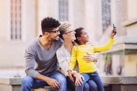 happy young mixed race couple having fun with little daughter and taking selfie