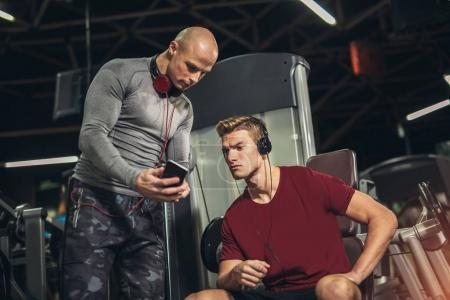 young sporty man and personal trainer with tablet pc in gym