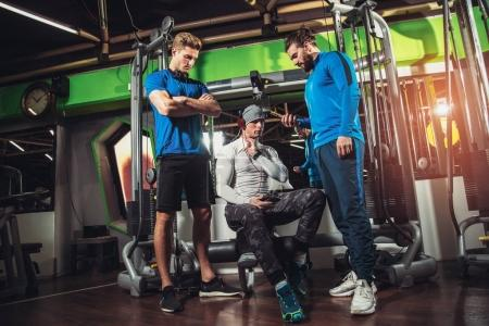 young sporty men and personal trainer with tablet pc in gym