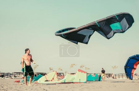 portrait of active man preparing sport equipment kitesurfing