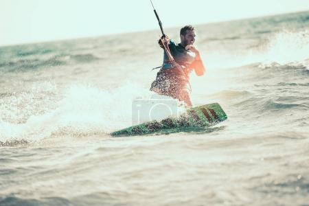 active man kitesurfing among sea waves