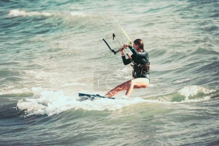 active woman kitesurfing on sea waves