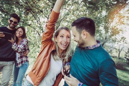 group of young happy friends having fun in spring park