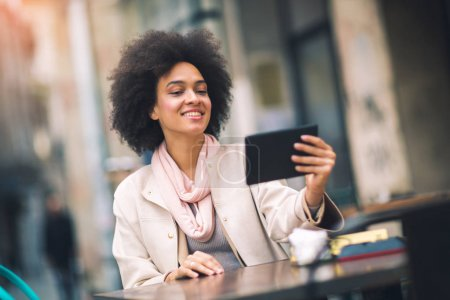 african american young happy businesswoman using digital tablet sitting at city cafe