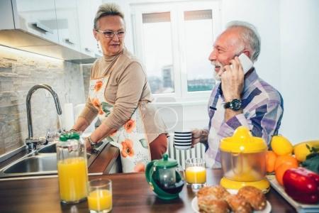 Elderly couple in the kitchen preparing breakfast, man using phone