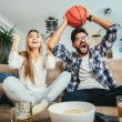 Couple is watching basketball game on the sofa at home.