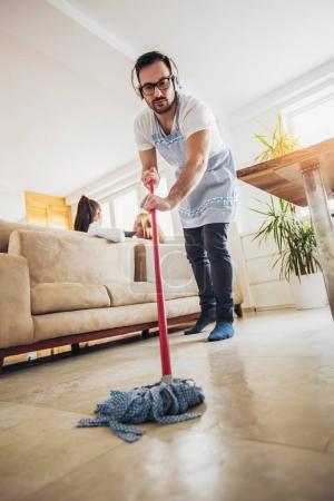 Photo pour Concept de ménage et de nettoyage du mari. Un homme nettoie la maison, tandis que les femmes bavardent sur le canapé - image libre de droit
