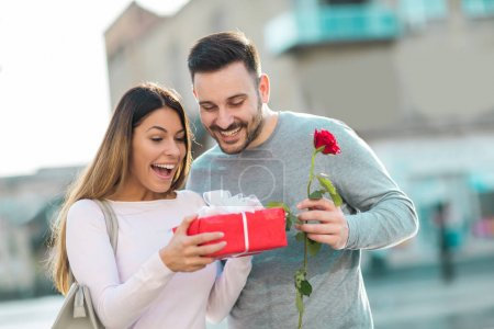 Happy couple on Valentines day. Young man gives a gift to young