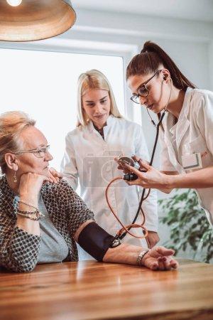 Bild eines jungen Sanitäters, der beim Hausbesuch Blutdruck nimmt