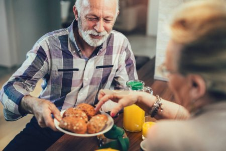 Elderly couple in the kitchen preparing breakfast