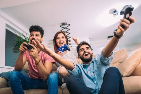 Photo for Group of young friends play video games together at home. - Royalty Free Image