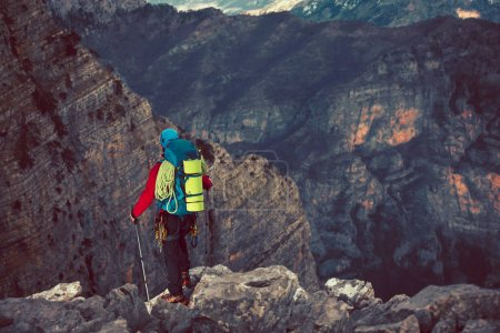 Young mountaineer standing with backpack on top of a mountain and enjoying the view