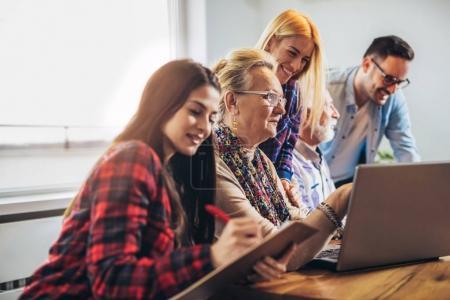 Photo pour Jeunes volontaires aident les personnes aînées sur l'ordinateur. Jeunes gens assura seniors introduction à internet - image libre de droit