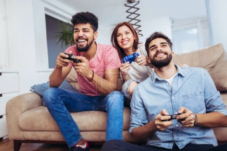 Group of young friends playing video games together at home.