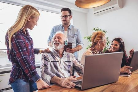 Young volunteers helping senior people to using computer.