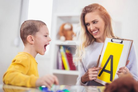 Photo for Speech therapist teaching boy to say letter A - Royalty Free Image