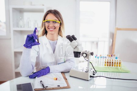 Young female scientist holding test tube with blood sample making research in clinical laboratory