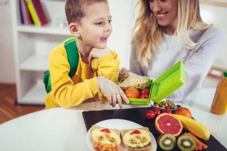 Mother making breakfast for her child in morning and snack for school