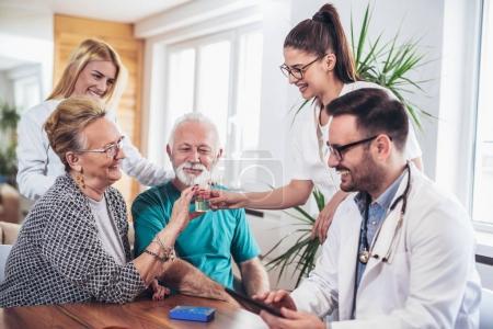 Seniorenpaar im Gespräch mit Gesundheitsbesuchern zu Hause. Sie sprechen über verordnete Therapie und geben der Krankenschwester Urinprobe.