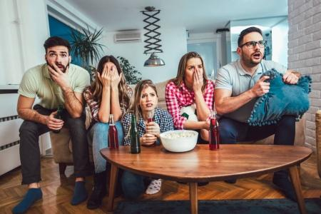 Happy friends or football fans watching soccer on tv at home.Friendship, sports and entertainment concept.