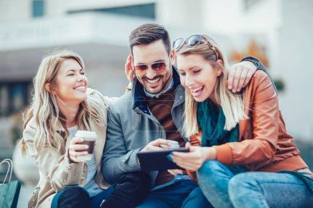 Grupo de amigos riendo con tableta digital al aire libre