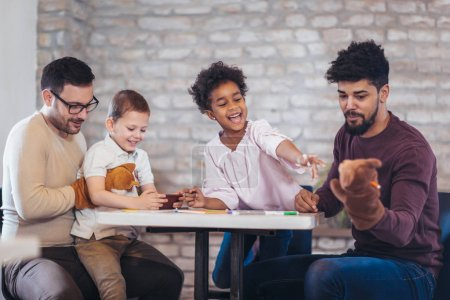 Photo for Two fathers with children having fun while playing with hand toys at desk - Royalty Free Image