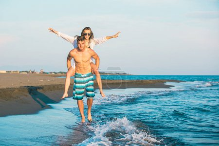 Photo for Happy couple in love on beach summer vacations. Joyful girl piggybacking on young boyfriend  having fun. - Royalty Free Image