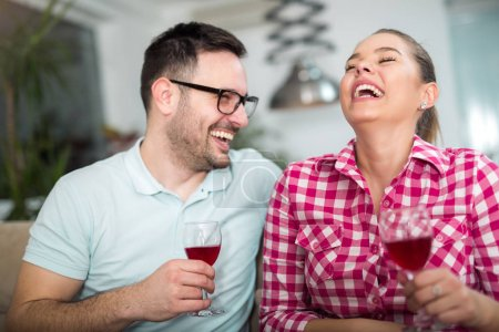 Photo of a young cheerful couple toasting at home with wine.