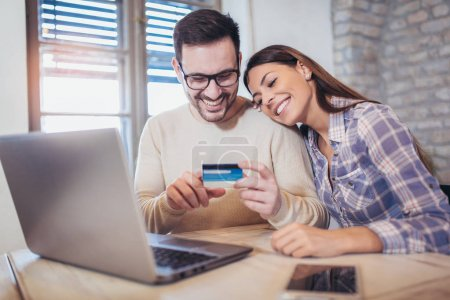 Young couple with laptop and credit card buying online.